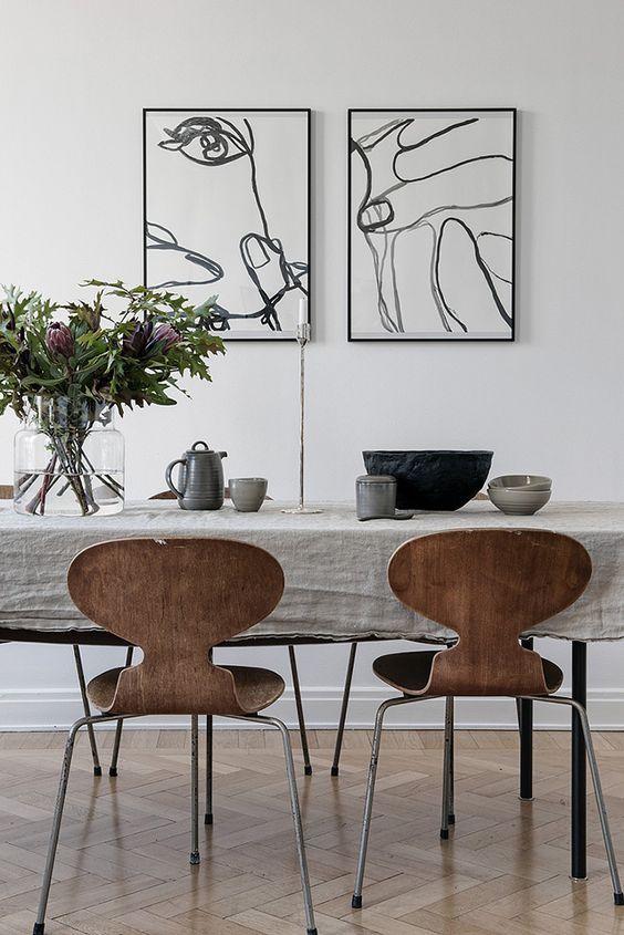 Scandinavian style dining room | rustic linen tablecloth with arne jacobsen seven chairs | modern wall art | wooden herringbone floors