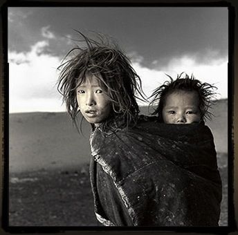 Jigme,8 Sonam,18months,Ladakh,Tibet     Jigme and Sonam are sisters whose nomadic family had just come down from the Himalayan highlands to their 16,500 ft. winter camp on the Tibetan Plateau. When I gave Jigme a Polaroid of herself she looked at it, squealed and ran into her tent. I assumed that this was one of the only times she had seen herself since her family did not own a mirror.         Words and Photograph by Phil Borges.