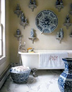 """An otherwise neutral bathroom decorated with blue and white porcelain. Note too the """"chopstick"""" or """"chinois"""" style monogram on the towels."""