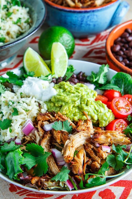 Healthy chicken carnitas burrito bowls with cilantro lime cauliflower rice, bean, tomatoes and guacamole