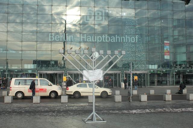 X-MAS - De Chanoekia en de kerstboom langs elkaar in het centraal station van Berlijn.