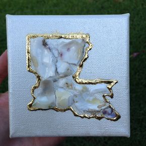 Crushed oyster shells in the shape of Louisiana on a mini 4x4 or 6x6 acrylic pearl painted canvas The state of Louisiana is outlined in metallic gold leaf Thin coat of varnish applied to shells to give them to sheen Perfect for: Your desk at work Home decor Bed side table Bridesmaid gift Hostess gift Birthday gift Looks great sitting on a shelf or hanging in wall grouping