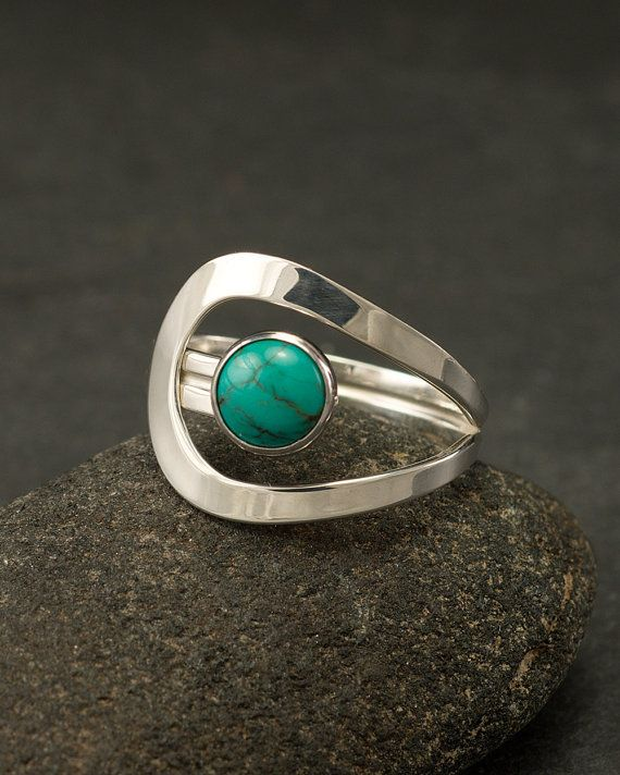 This argentium sterling silver ring is a simple round band that has a curving line which accentuates a 6mm natural turquoise gemstone. This ring was