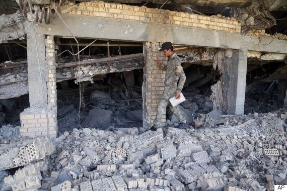 An Iraqi soldier inspects the demolished tomb of former Iraqi president, Saddam Hussein, in Tikrit, north of Baghdad, Iraq