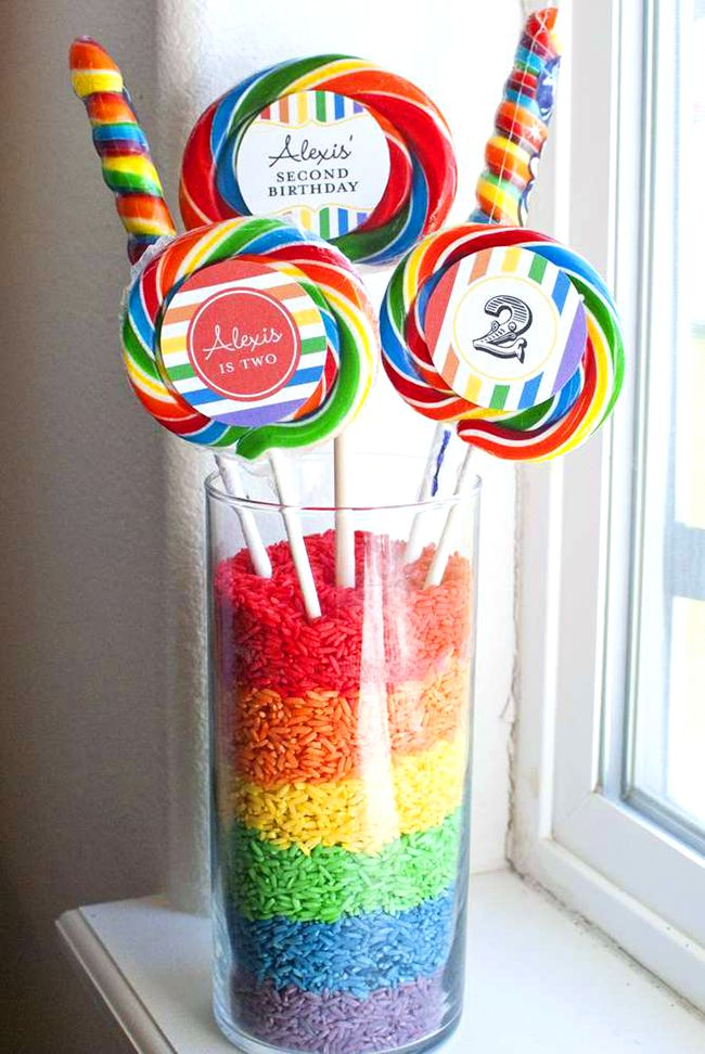 Bright and pretty rainbow theme birthday party - Centerpieces made from candy and rainbow rice!