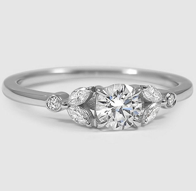 This feminine, nature-inspired ring features four dazzling marquise shaped diamonds elegantly accenting a center diamond.