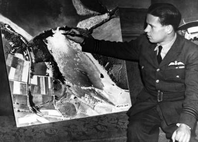Guy Gibson with a large aerial photograph of the Mohne Dam taken after the Dams Raid.