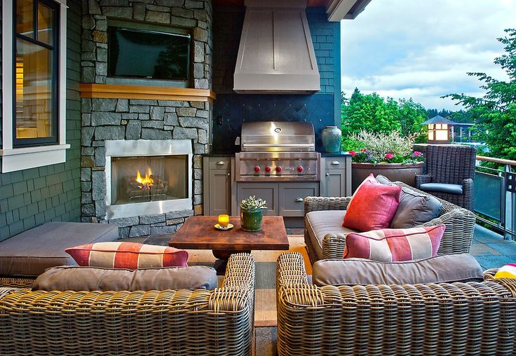 Outdoor kitchen design with cozy sofa, tv, and fireplace