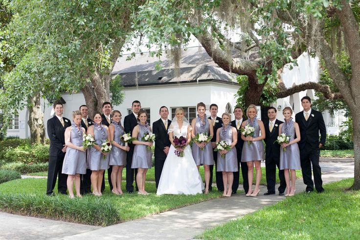 the wedding party gathers outside the chapel. bridesmaids in lavender dresses and carrying white bouquets and groomsmen in black tuxedos make this a classically beautiful picture under moss draped oak trees.