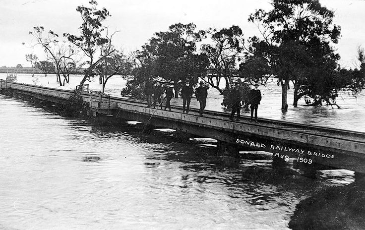People standing on a railway bridge at Donald amidst floodwaters in August 1909.