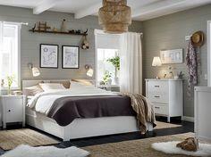 Kis hálószoba, fehér ággyal, fehér fiókos szekrények és éjjeliszekrények.