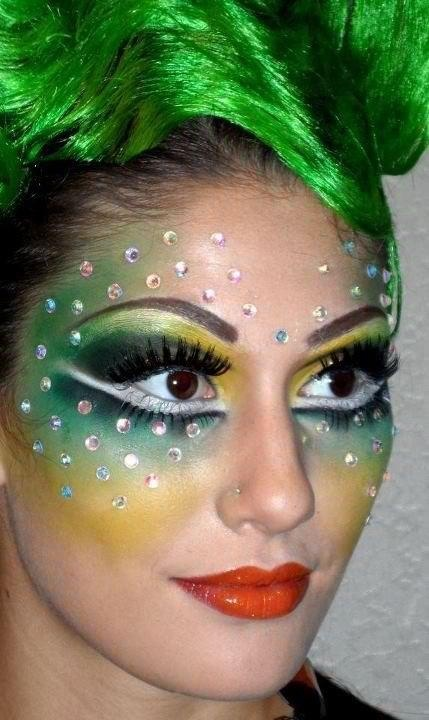 Green, yellow, black and white make-up with a mask of crystals.