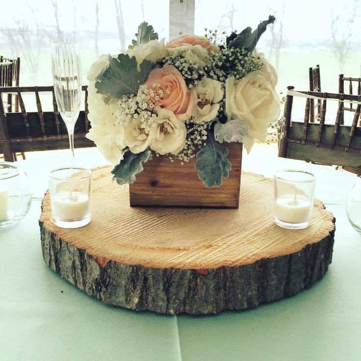 A rustic, romantic wooden planter box centerpiece created by Courtney Inghram Events, a Virginia-based wedding floral designer and planner. Blush, Ivory and Dusty Miller colors, with blush garden roses, hydrangea, peach Tiffany roses and baby's breath on a slab of wood! Sweetheart table inspiration for a tented reception outdoors. Romantic boxes overflowing with flowers for wedding reception. Maryland outside wedding at Walkers Overlook. Centerpiece with votives around it.
