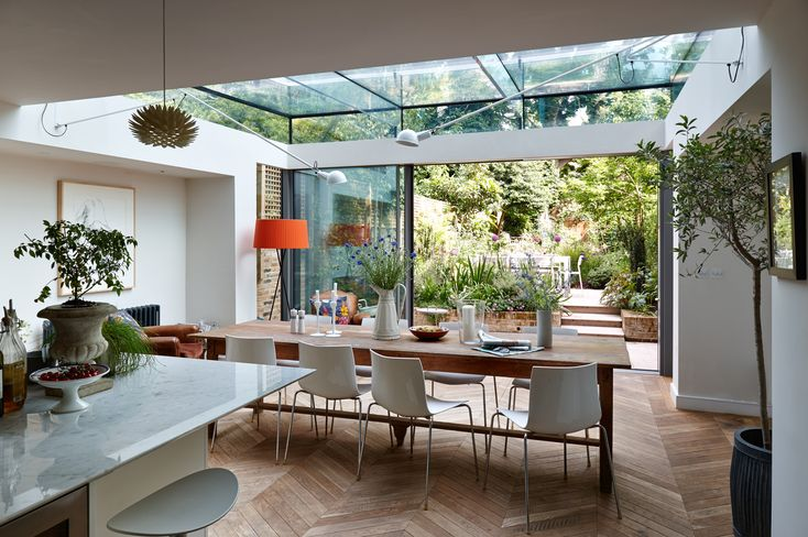 Trombe - Internal photo of a dining room extension in London. It incorporates a structurally glazed roof supported on laminated glass fins and beams. The extension has minimal frame sliding doors to maximise the views to a picturesque garden. The glass has heat mirror technology to provide a comfortable internal environment. Due to the glass ceiling some flos cantilevered lights have been installed