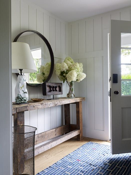 Modern farmhouse style in an entryway design featuring a large rustic wood side table, a round metal framed mirror, and a unique ceramic lamp - Home Decor & Decorating Ideas - apartmenttherapy.con