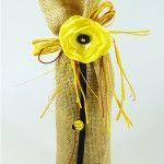 Jutowy worek na wino z żółtym kwiatem i guziczkiem stonką-biedronką, wiązany rafią. Burlap wine bag with yellow fabric flower and ladybug batton.