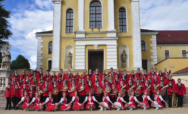 """Hrubos Zsolt   """"Mórikum"""" zenekarunk Nagyon büszkék lehetünk a Móri Ifjúsági Fúvószenekarra, a Móri Ezerjó, kvircedli és még egy sor helyi értékünk mellett a város őket is a mórikumok közé sorolja. A kép a Kapucinus templom előtt készült. A zenekar olaszországi turnén vesz részt és a dunaföldvári Löfan mazsorett csoporttal. Sok sikert, biztosan az olaszokat is elkápráztatják műsorukkal! Több kép Zsolttól: www.facebook.com/zsolt.hrubos és www.hrubosfoto.hu"""