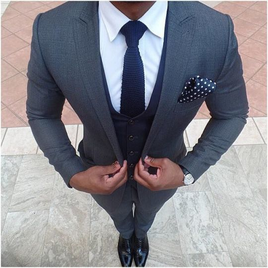 Something as simple as opting for a dark grey suit and a navy blue waistcoat can potentially set you apart from the crowd. Why not add black leather brogues to the mix for a more relaxed feel?   Shop this look on Lookastic: https://lookastic.com/men/looks/suit-waistcoat-dress-shirt/19207   — White Dress Shirt  — Navy Knit Tie  — Navy and White Polka Dot Pocket Square  — Navy Waistcoat  — Charcoal Suit  — Black Leather Brogues