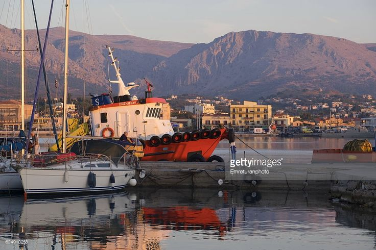 sailboat and a tug boat anchored at port of chios at dawn on a sunny autumn day with hills at the background.