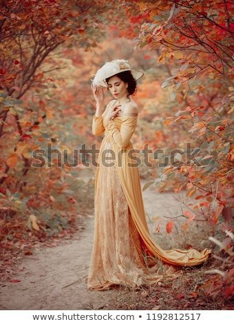 A young brunette woman with an elegant, hairstyle in a hat with a strass feathers. Lady in a yellow vintage dress walks through the autumn landscape