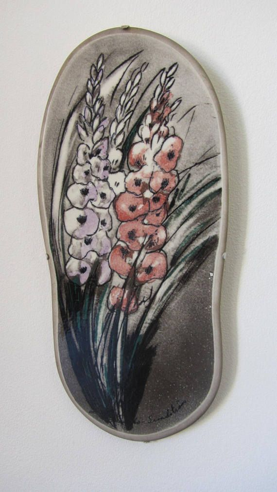 Vintage ceramic/porcelain wall plaque, with a flower design by Heljä Liukko-Sundström, made in the 1980s and manufacturated by Arabia of Finland. This stunning oblong plaque features, with great detail, a bouquet of flowers in gray, with pink and purple subtle details. Hand signed by the artist in the front lower part of the plaque. Stamped ARABIA FINLAND in black on the back. Has the original metal hanger. Arabia produced this type of plaques in two different dimensions. This one is the...