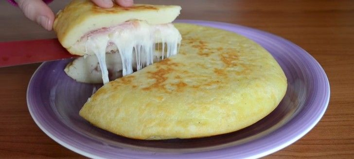 A Potato, Egg, Ham and Cheese omelette. Potatoes, egg, and flour are mixed together to form a dough in which the cheese melts and the ham is cooked inside.
