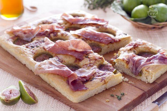 La focaccia al crudo e fichi è uno stuzzicante snack dal sapore agrodolce preparato con ingredienti saporiti e di stagione.