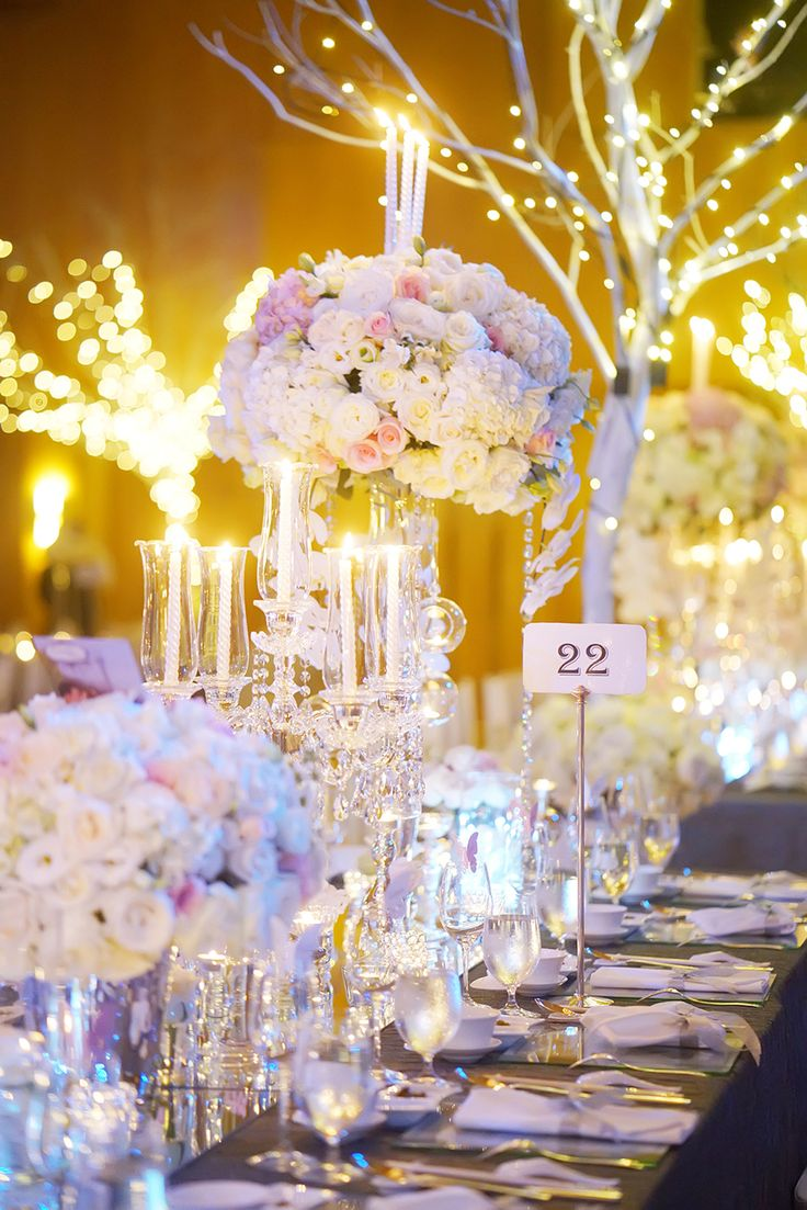 Pastel-coloured floral centrepieces and table number with silverware // Ken and Jessica's magical Disney celebration put us under a spell and the enchantment continues with their Ritz-Carlton ballroom wedding banquet photographed by Lightedpixels Photography and planned by Our Fairytale Wedding, with its unforgettable entrance by the bride in light-up fairy wings and cake-cutting ceremony highlighted with pyrotechnics.