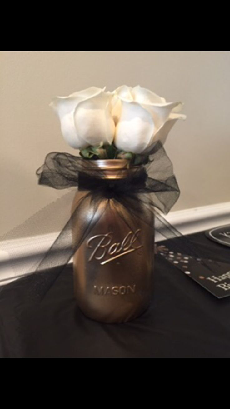 Gold mason jar centerpiece with black tulle bow and white roses; vintage centerpieces, mason jar centerpieces, milestone birthday centerpieces