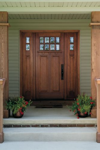 Wood doors and sidelights with beveled glass create a welcoming ...