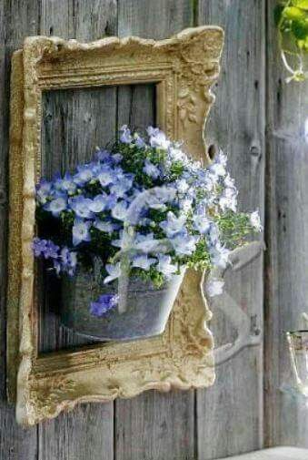 Love this! Framed flowers hung on a fence.