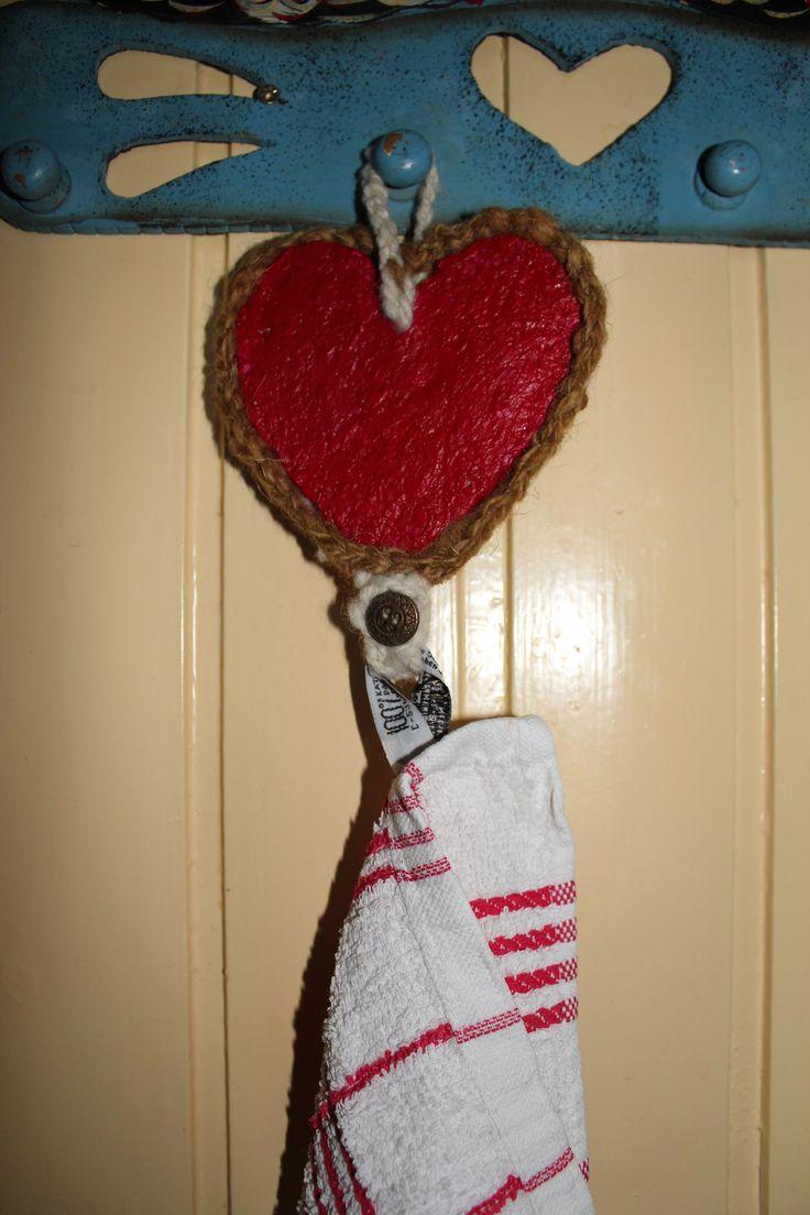 Een hart van papiermaché met een gehaakte rand erom heen en een lus met een knoop waar de handdoek aan kan.