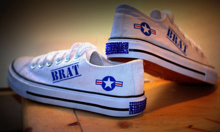 """Give those high heels a break! Don't be limited to just T-shirt -n- Jeans, you can wear these with a sundress or maxi skirt. White canvas shoes feature a military style """"BRAT"""" stamp with matching Air Force insignia. On the back of shoe is a tab full of gorgeous matching sapphire rhinestones.  ..."""