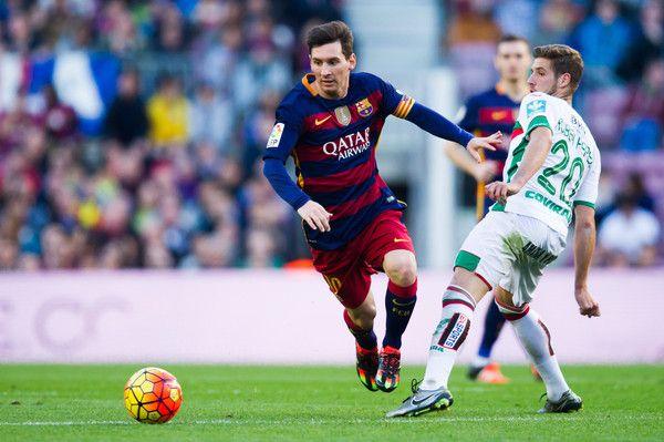 Lionel Messi of FC Barcelona conducts the ball past Ruben Perez of Granada CF during the La Liga match between FC Barcelona and Granada CF at Camp Nou on January 9, 2016 in Barcelona, Catalonia.