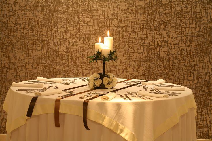 Στολισμός τραπεζιού καλεσμένων με Classy style, Το τραπέζι έχει διακοσμηθεί με ένα κηροπήγιο με τρία μεγάλα λευκά κεριά που τα αγκαλιάζει όμορφα κισσός, καθώς και δύο μπουκετάκια με λεύκα τριαντάφυλλα στη βάση του κηροπήγιου.