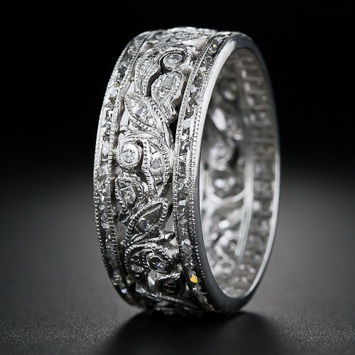 This 1930s vintage all-around (eternity) platinum and diamond wedding band is essentially comprised of three distinct rings. The central band is crafted in a fanciful diamond-set foliate design and is book-ended by a pair of very narrow eternity bands twinkling with teeny-tiny French-cut diamonds. A sweetheart in an un-sizable size 6.