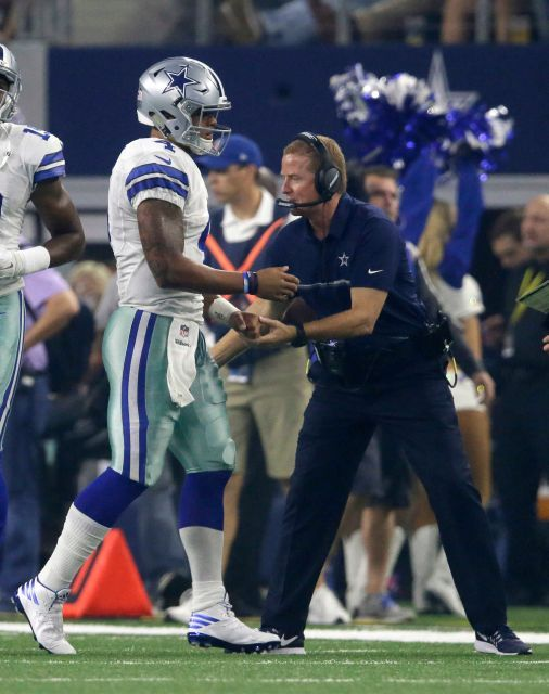 Dallas Cowboys' Dak Prescott is congratulated by head coach Jason Garrett, right, after Prescott scored a touchdown on a running play against the Chicago Bears in the first half of an NFL football game, Sunday, Sept. 25, 2016, in Arlington, Texas.