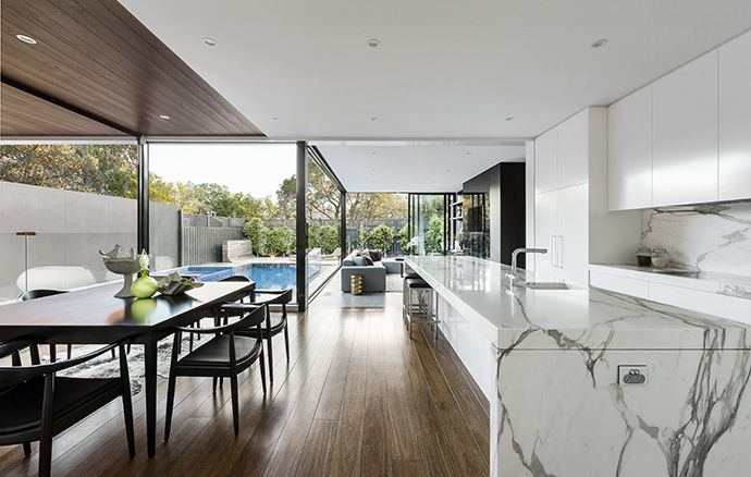 This lovely white kitchen transitions into a wood dining room wrapped in glass, with the luxurious pool visible in the backyard. The island is covered in white marble with thick gray veins.