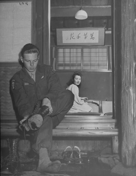 US soldier joining a Japanese girl in off-limits dinner, taking off his shoes. Japan, 1946. Photo by John Florea. S)