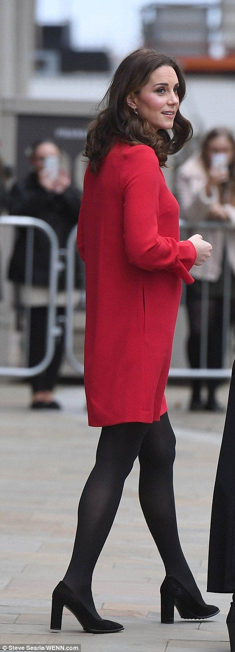 After arriving bundled up in a grey coat, she revealed a very cheerful red dress underneath