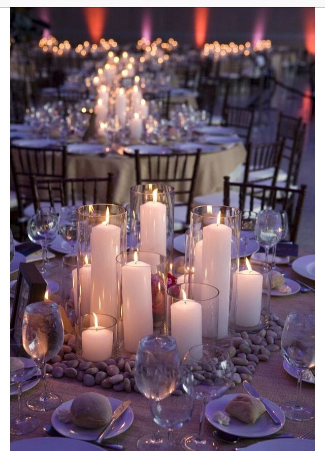 The centerpiece will have candles like this and framed with silver dollar euc and flowers lightly spraying from in between the candles