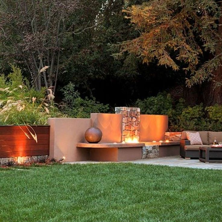 Gather around a firepit wall  Overlapping panels of ipe wood and colored concrete flank the firepit in this backyard in Los Altos Hills, California. Stone veneer forms a chimneylike background for the flames, creating a classic focal point for this true outdoor living room. Plant living torches. Golden flower plumes of Miscanthus sinensis shimmer and sway over grassy leaves. Add shadow casters. Small well lights positioned close to the dark walls create contrasting pools of warm light…