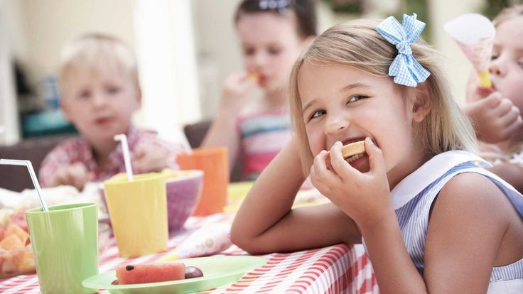 Girl at a birthday party munching an apple
