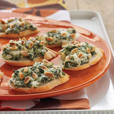 Spinach and Parmesan Crostini's   Prepare the spinach-and-cheese mixture up to a day ahead.  10-oz pkg frn spinach, thawed   8-oz pkg cream cheese, softened   1 c freshly grated Parmesan cheese   1/4 c mayonnaise   1 large garlic clove, minced   1/4 tsp freshly ground pepper   1/2 (16-oz.) French bread loaf, cut diagonally into 1/2-inch slices   1/3 c pine nuts  325 degrees for 10 min