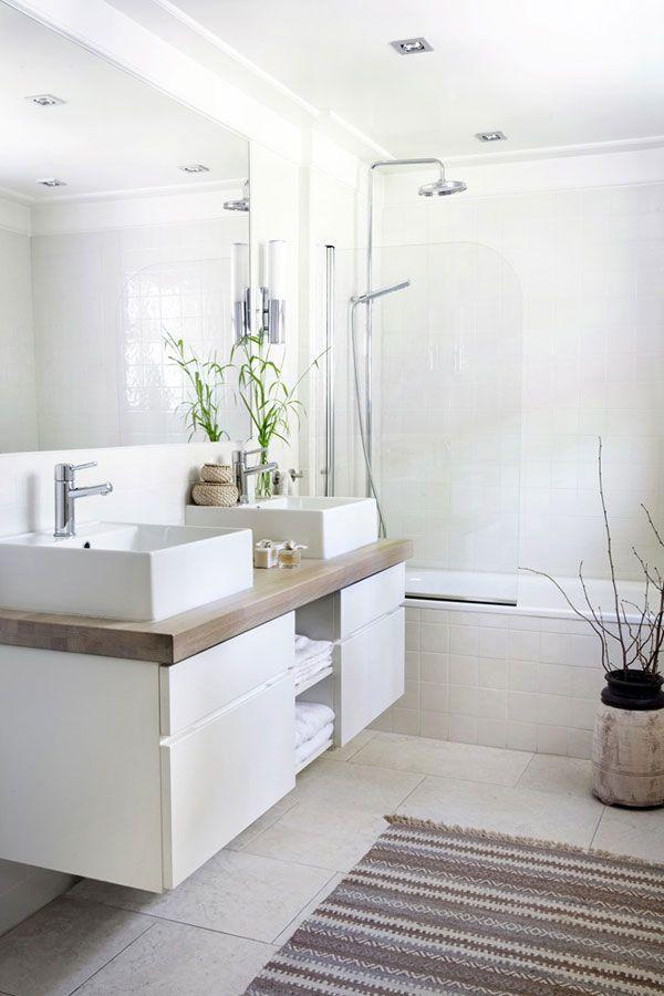 azulejos, sanitarios y muebles blancos combinado con encimera de madera