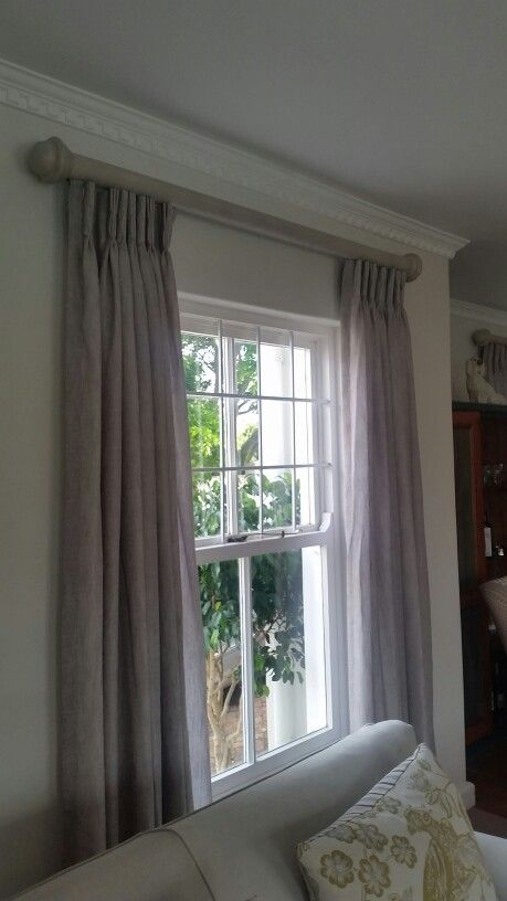 Pinch pleat lined curtains on wooden recessed track with paint effect.