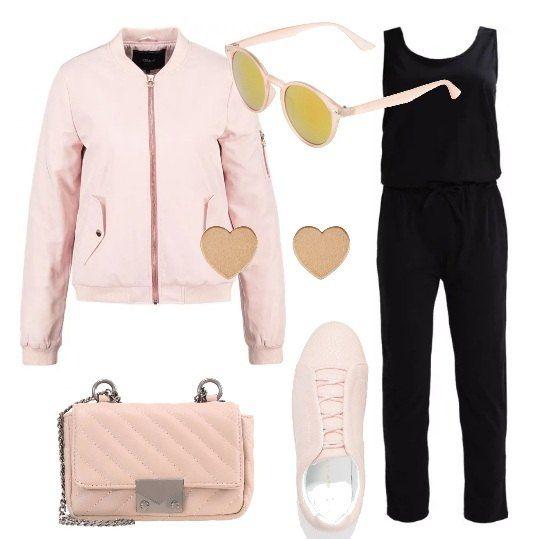 La tuta nera, in jersey di cotone con profonda scollatura sulla schiena, è abbinata al colore rosa: bomber con collo alla coreana, sneakers in ecopelle, tracolla in ecopelle e metallo, orecchini di metallo, a forma di cuore, occhiali a specchio.