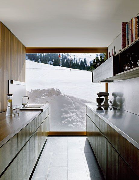 At Strolz House, the kitchen looks out onto the neighboring pastures, which are covered in a blanket of snow.