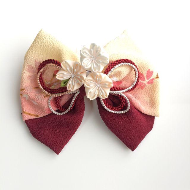 ✤ご覧頂きありがとうございます✤ ちりめん生地のりぼん(ポリエステル)に、正方形の小さな布を折りたたんで作るつまみ細工で作成した正絹の桜、3輪をUピンで添えました。リボンは縦約12cm、横約14cmでボリューム感があります。桜一輪の花の大きさは約3cmで...