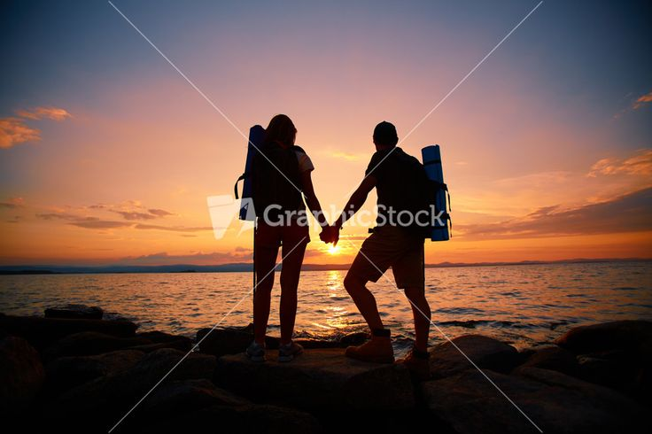 Image Of Beautiful Scene Of Sunset And Backs Of Couple Of Hikers Enjoying It Stock Image